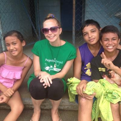 A volunteers takes a picture with children at her placement in Samoa